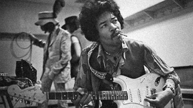 jimi hendrix playing guitar and smoking a cigarette