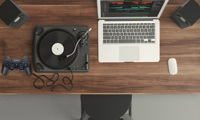 a joystick, a turntable and a laptop on a desk