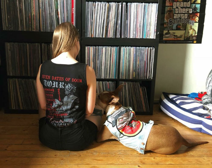 tanja and her dog in front of her vinyl collection