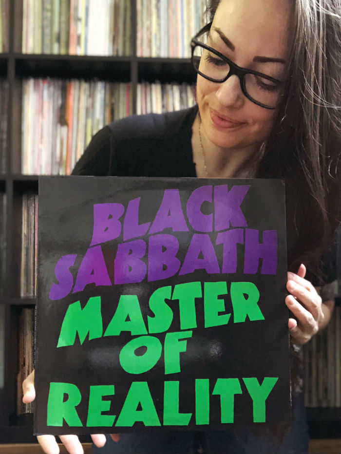 jenn holding a variante of master of really, black sabbath record